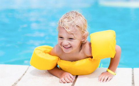 smiling child climbing out of pool with bright yellow float