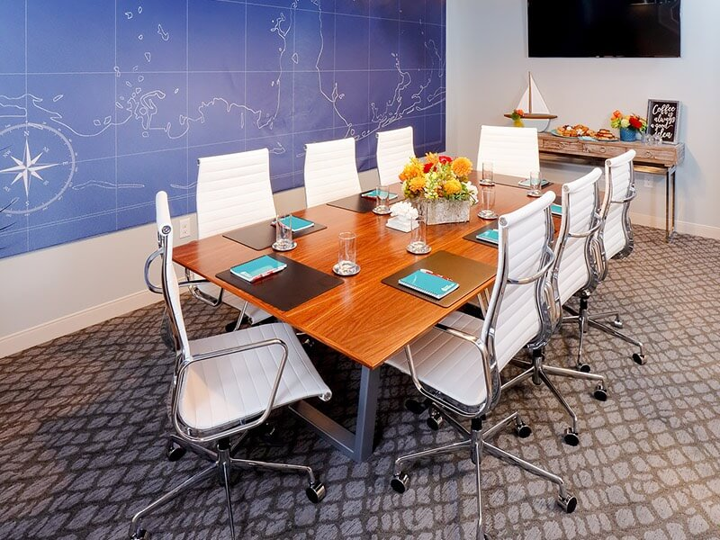 meeting room setup with executive table and white chairs