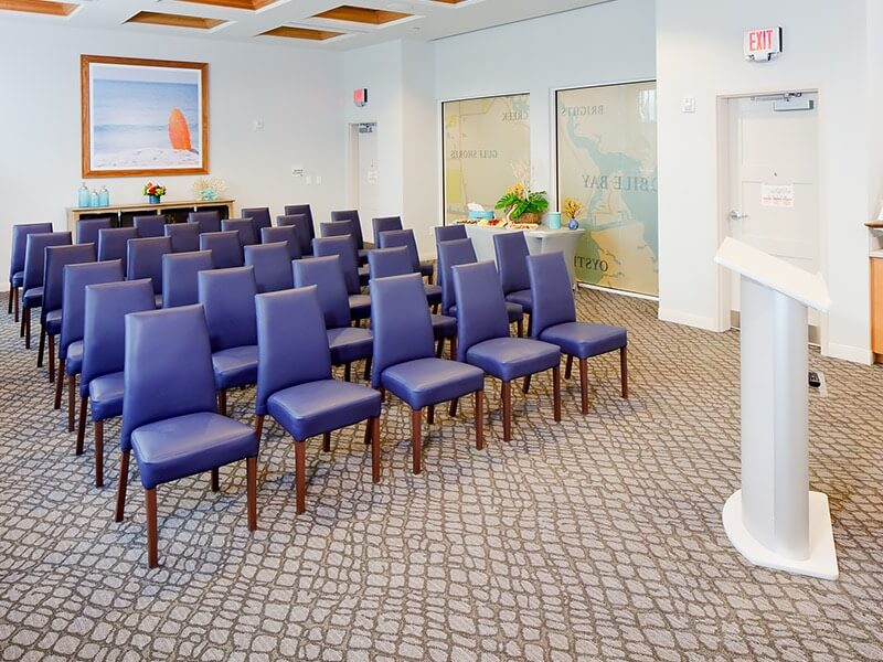 rows of blue chairs setup in a meeting space