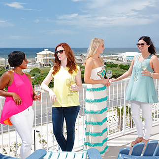 group of women standing on balcony enjoying cocktails on a clear day