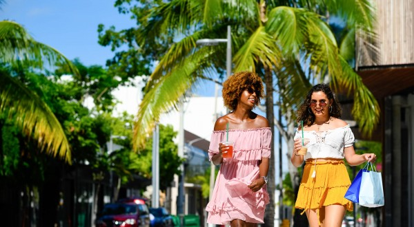 two women with shopping bags walking down street