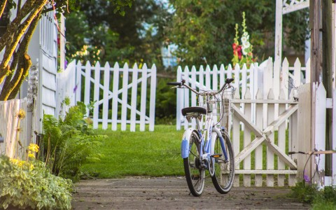 white and blue cruiser bike in front of a white picket fence