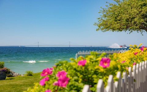 view of the water from behind a white picket fence