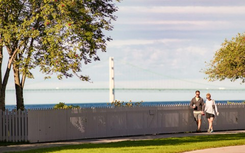 couple walking next to white picket fence overlooking the water