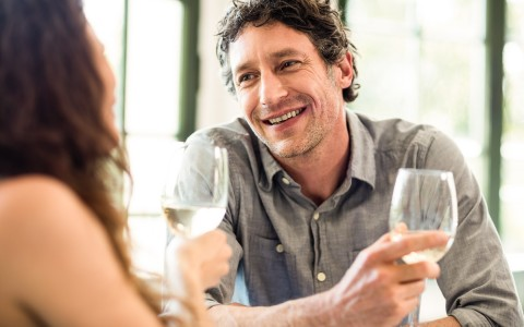 man looking at woman while holding a wine glass