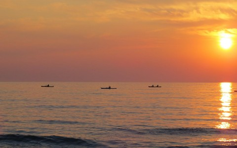 group of people kayaking in the middle of the ocean during sun down