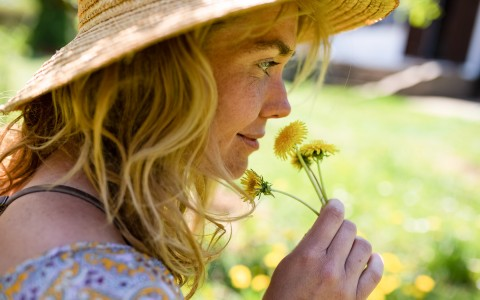 woman smelling yellow flowers
