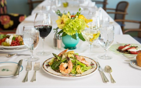 a shrimp dish on a plate on a table set up for an event with glasses of wine