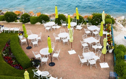 tables and chairs set up outside next to the ocean