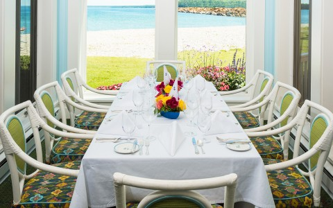 a dining table set up for an event, beach view in background