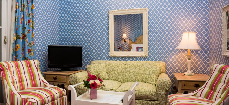 Blue room with striped chairs and floral green couch