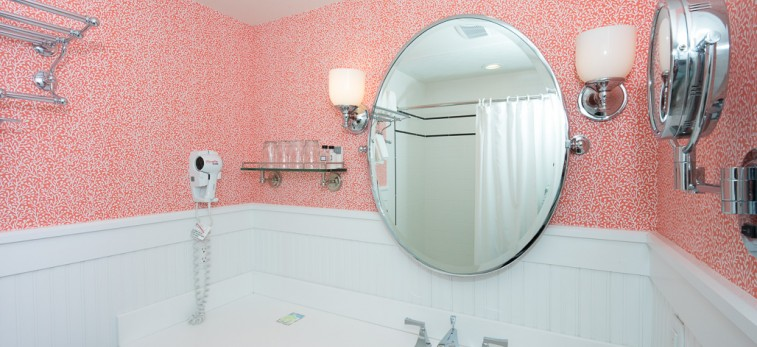 bathroom with pink wallpaper and large round mirror above white sink and countertop