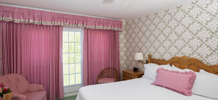 bedroom with white bed, pink accents, flower printed walls