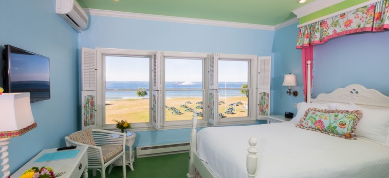 pale blue room with king bed, vanity, TV & wall of window with ocean view