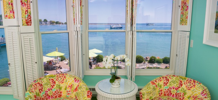 sitting area in turquoise room with yellow and pink floral chairs and ocean view through windows