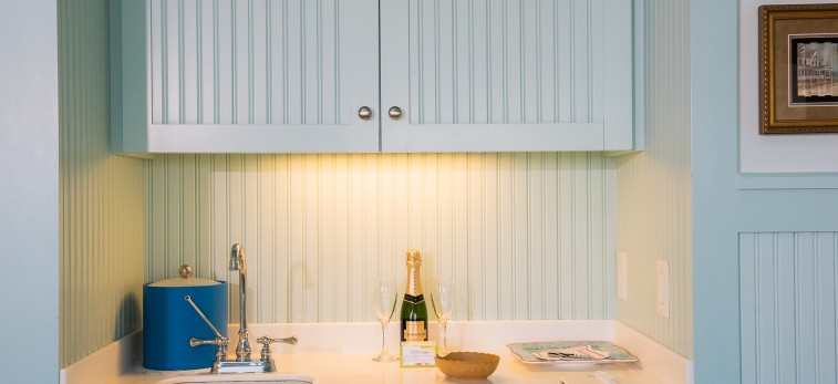 white cabinets with bottle of champagne sitting on the table
