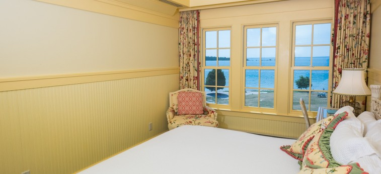 yellow room with white bedding and window with ocean view