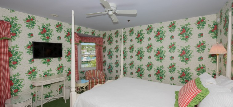 bedroom with flower printed walls, bed with red white and green accents