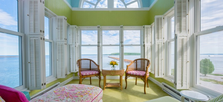 light blue and lime green bedroom with flowers and striped couches with green carpet