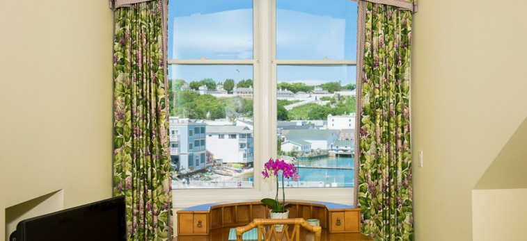 window outlooking building with flower curtains