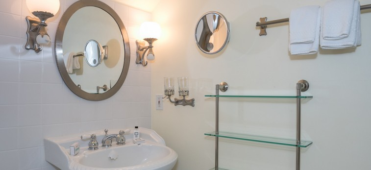 all white bathroom with small circle mirrors