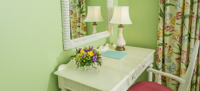 white desk in front of a large mirror on a lime green wall inside Hotel Iroquois room