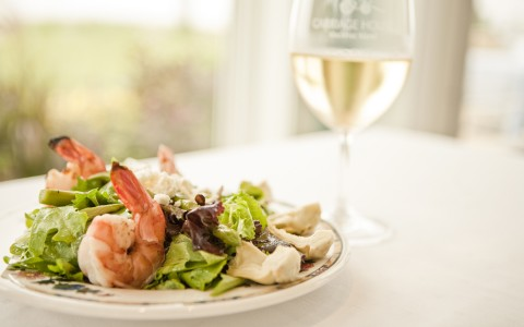 plate of salad with shrimp and glass of white wine