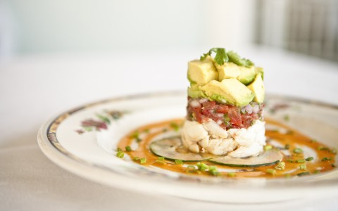 stacked salad of crab meat tomato and avocado on floral designed plate