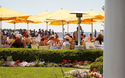 People seated outside in dining area with yellow umbrellas next to the ocean