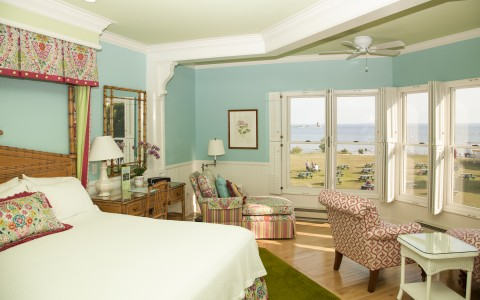 view of bed with flower accents, seating areas facing window with view of ocean