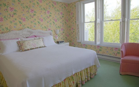 view of bed, flower accents on wall & pink chair next to window