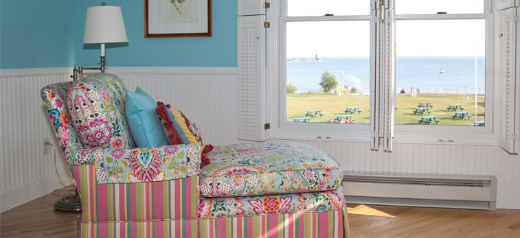Floral brightly patterned sofa facing white window panels