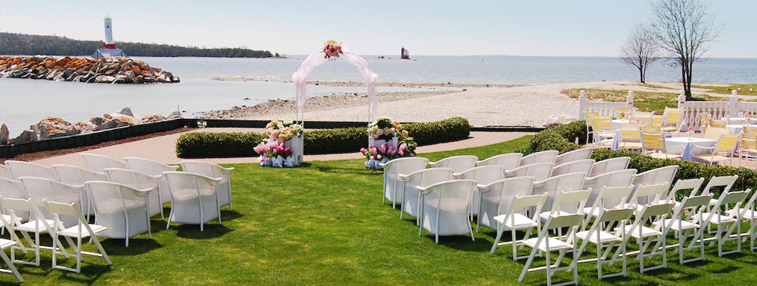 a wedding set up outside with the water in the background