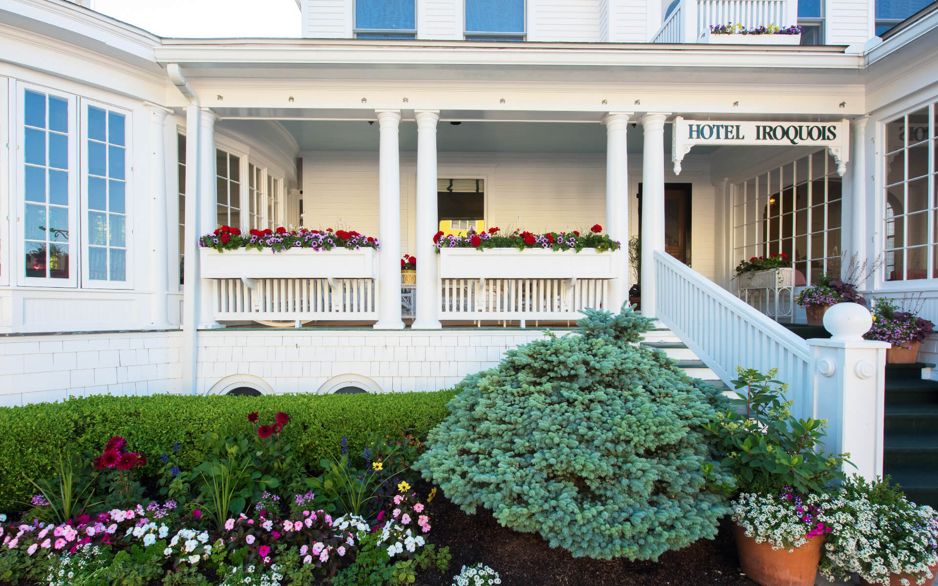 hotel iroquois entrance with porch, hedges, and pink and white flower landscaping