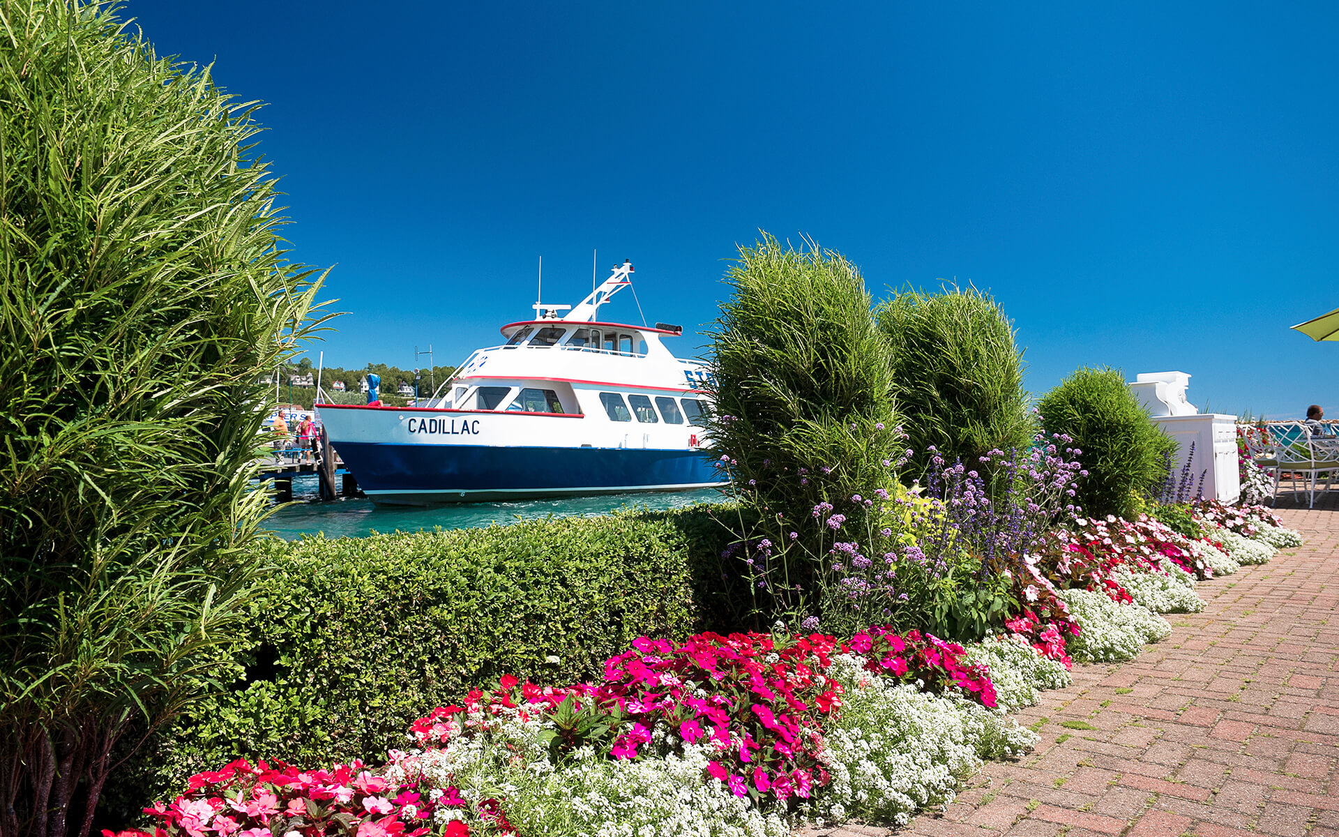 view of a yacht seen through hedges and pink floral landscaping