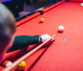 man playing on red pool table
