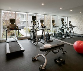 gym room with treadmills, elliptical machines and benches