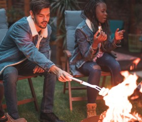 couple around a camp fire roasting marshmellows