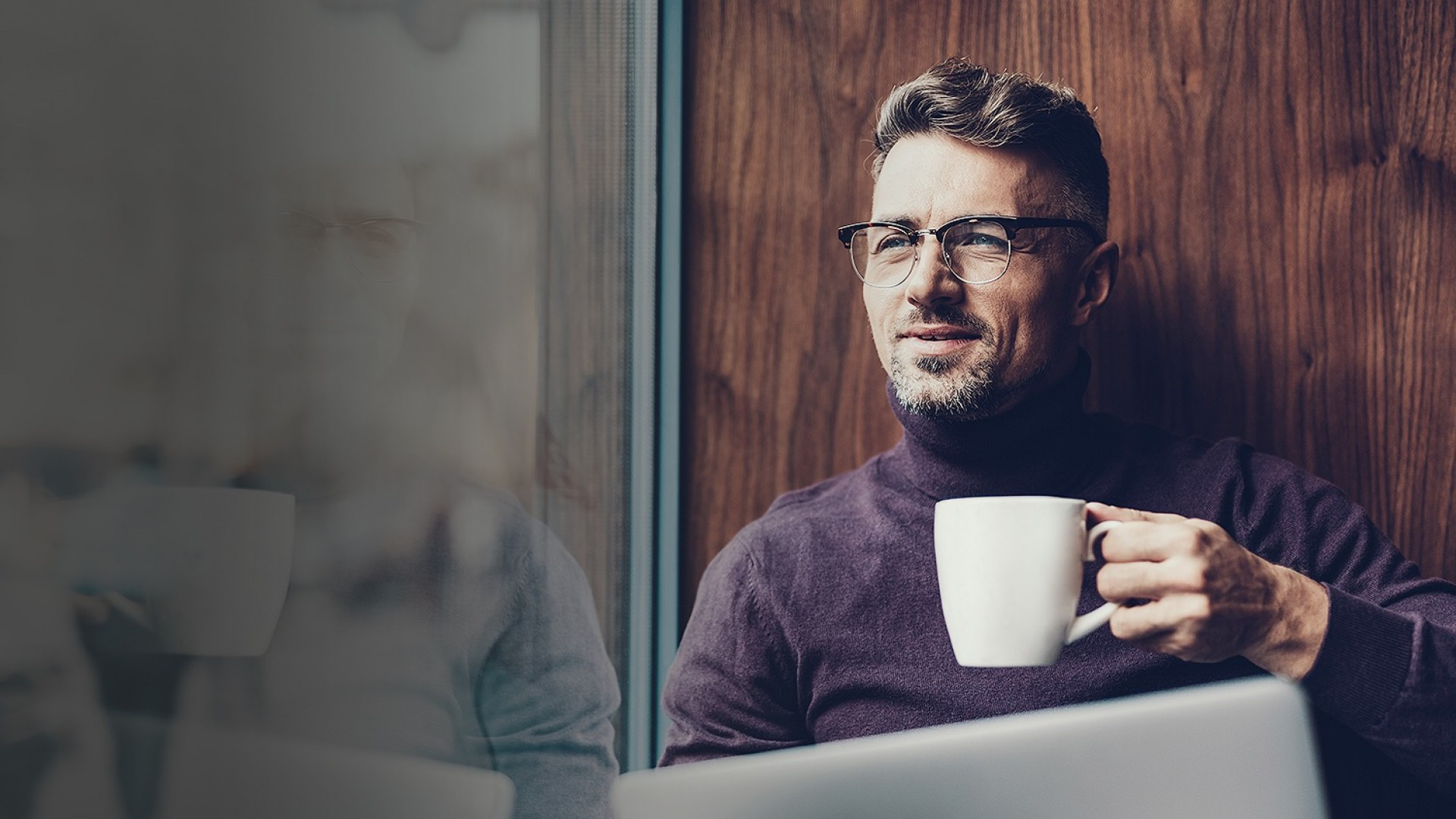 man working on computer while drinking coffee and looking through window