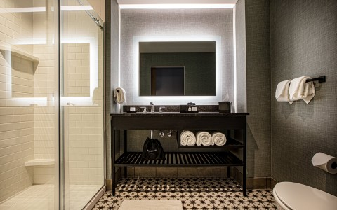 walk-in shower and vanity with backlit mirror