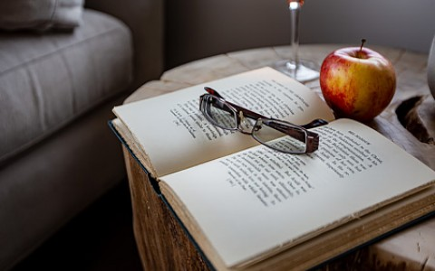 reading glasses sitting on open book