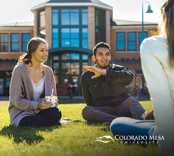 students sitting on lawn outside building