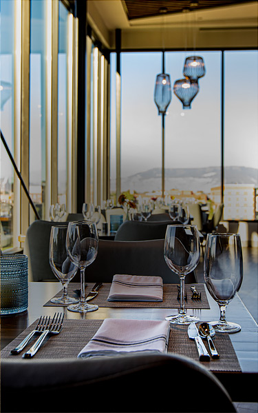 dining table set near floor to ceiling window with view of mountains