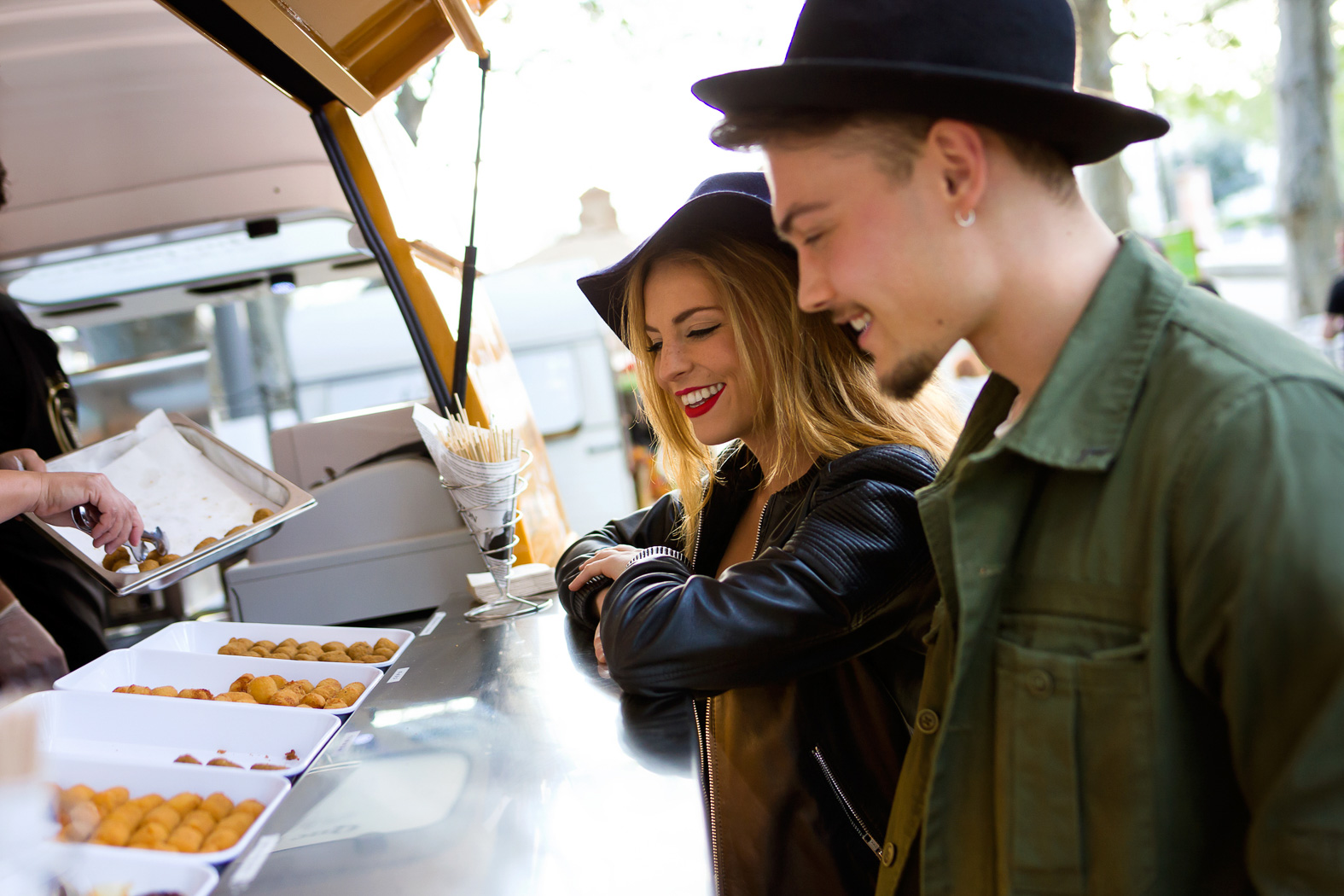 hipster couple standing at a food truck counter