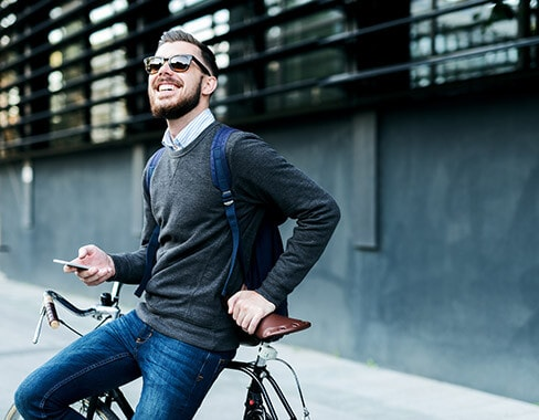 Man relaxing against bike on phone