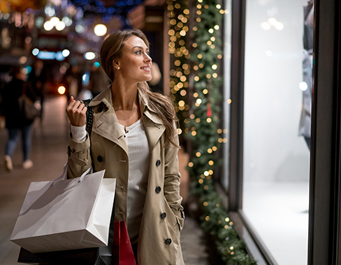 young woman holding shopping bags and window shopping the holiday displays in the evening