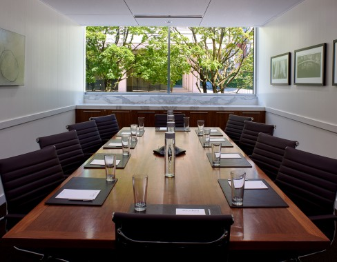 boardroom with place settings of notebooks and water glasses