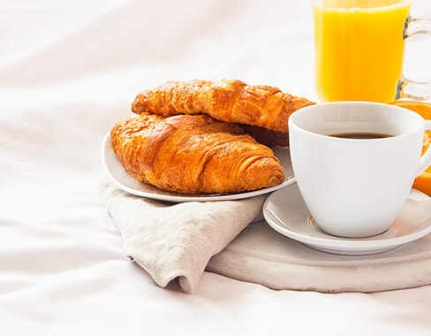 breakfast in bed with croissants coffee and orange juice