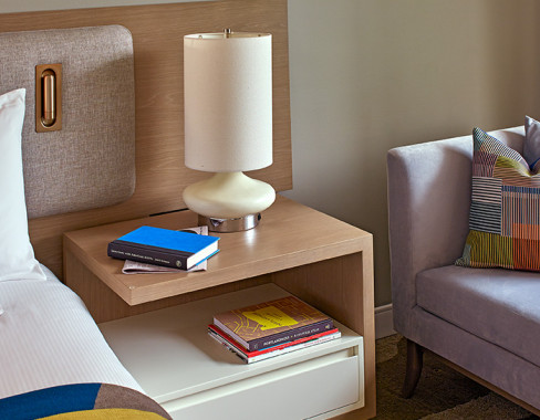 close up of the night stand in a guestroom with a book and a lamp