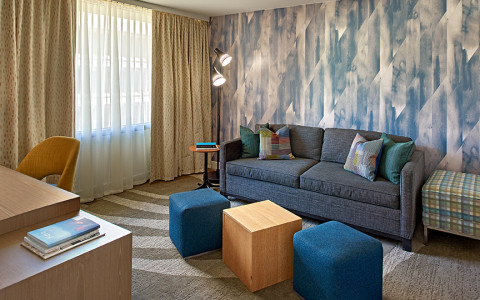 living room in the modera suite with blue patterned wallpaper and large couch